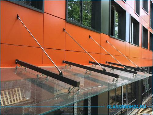 Длинный и большой козырек на фасаде здания оранжевого цвета